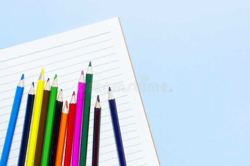 Crayons de couleur et carnet propre dans la ligne sur l'espace étendu plat bleu de copie de vue supérieure de fond Crayons coloré photographie stock libre de droits