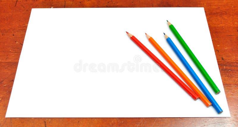 Crayons de couleur et livre blanc photo stock