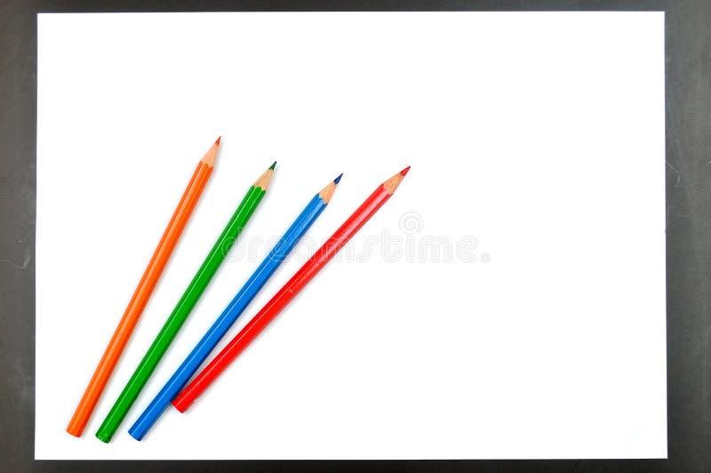Crayons de couleur et livre blanc photos stock