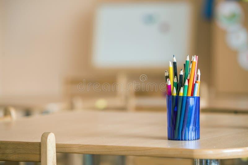 Crayons de dessin colorés en bois disposés dans la cruche en plastique sur le fond clair de l'espace de copie images stock