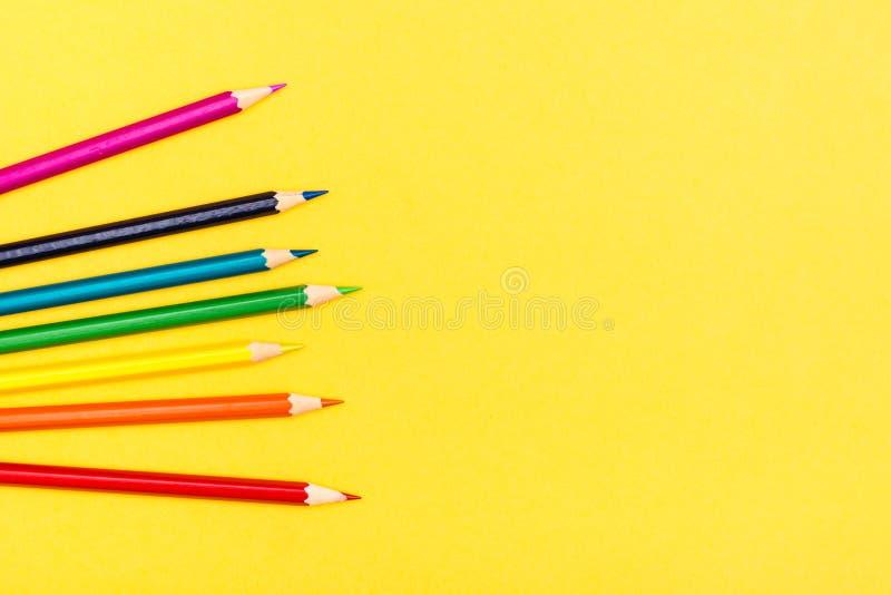 Crayons en bois colorés sur un fond jaune Palette d'arc-en-ciel images stock