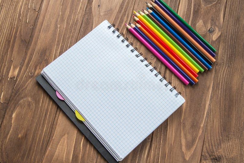 Crayons et bloc-notes colorés sur le fond en bois photographie stock libre de droits