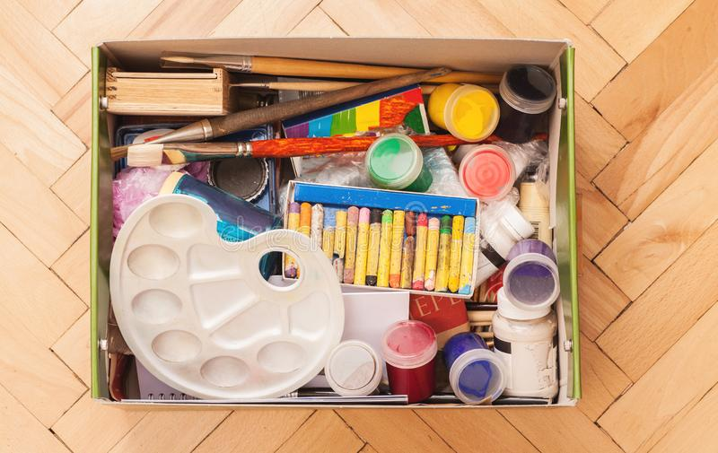 Crayons, gouache, paint brushes, pallet and other drawing stuff folded in box, top view royalty free stock photo