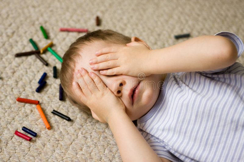 Crayons Kid. A little kid on the floor with colorful crayons, covering his eyes with hands royalty free stock photos
