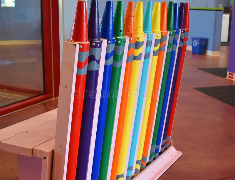 Crayons made of colorful steel made into a children`s play bench. A child`s play area bench made of colorful steel poles shaped like crayola crayons in assorted royalty free stock photo