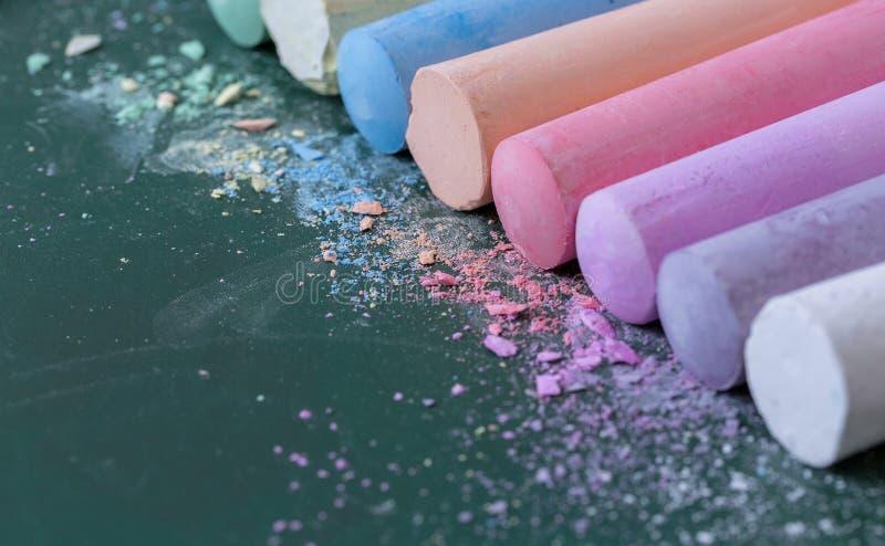 Crayons multicolores, en pastel Vert, jaune, rose, pourpre, bleu Pastels peints Craie renversée sur un conseil vert images libres de droits