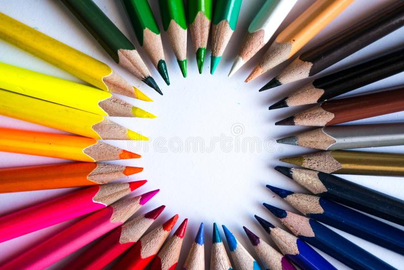 Crayons multicolores formant un cercle de couleur d'isolement sur le fond blanc photo stock
