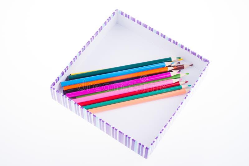 Crayons multicolores lumineux dans une boîte rayée Badine le retrait initial de main d'art images stock
