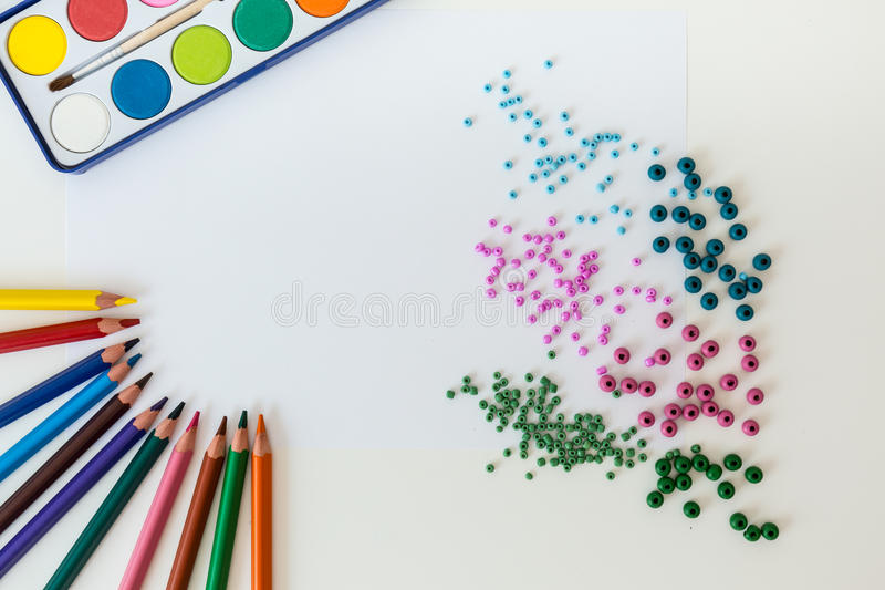 Crayons and paints on a table stock images