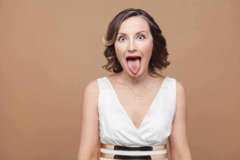 Crazy adult woman with big eyes tongue out. Emotional expressing woman in white dress, red lips and dark curly hairstyle. Studio shot, indoor, on beige or stock photos