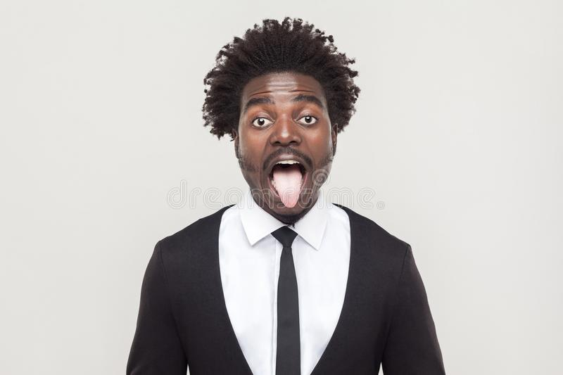 Crazy afro man looking at camera and tongue out. Studio shot, gray background stock image
