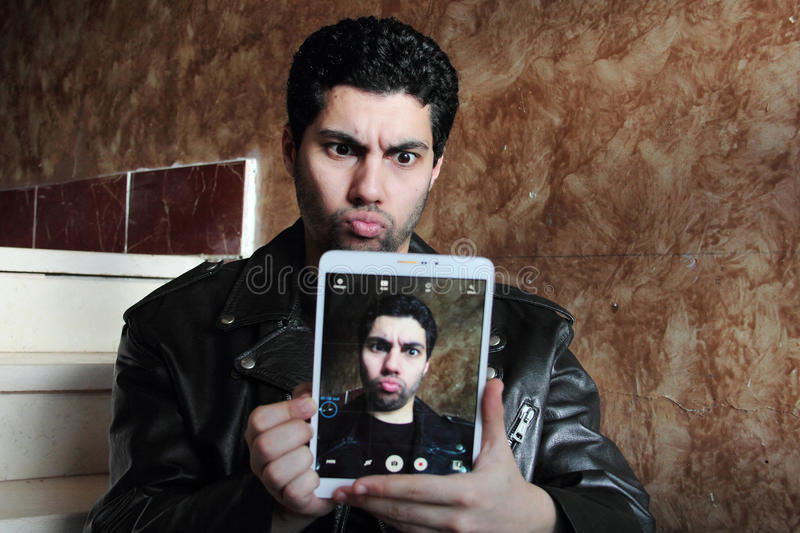 Crazy arab young businessman in jacket taking selfie stock photos