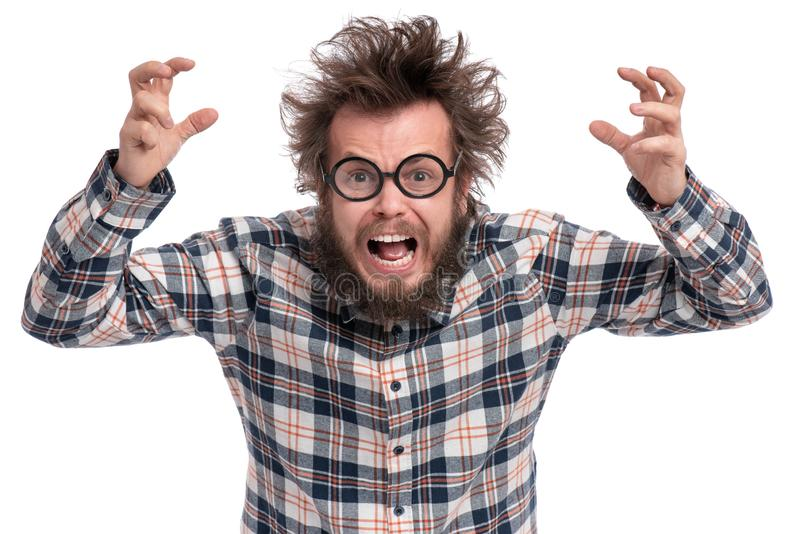 Crazy bearded man emotions and signs. Crazy angry Man with funny Haircut in Eyeglasses. Bearded Enraged furious guy in plaid shirt screaming in anger, isolated stock image