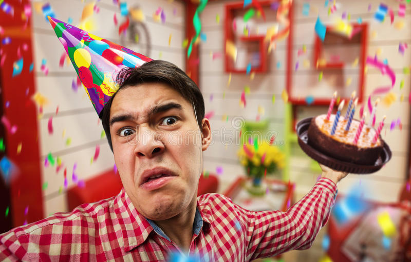 Crazy birthday boy. With cake in his hand stock photography