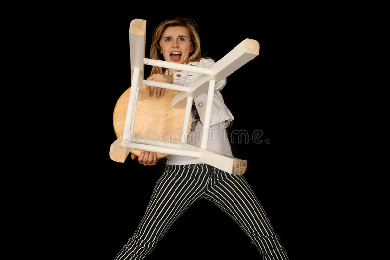 Crazy blond woman holding a bar stool out like a lion trainer. Crazy woman holding a bar stool out stock image