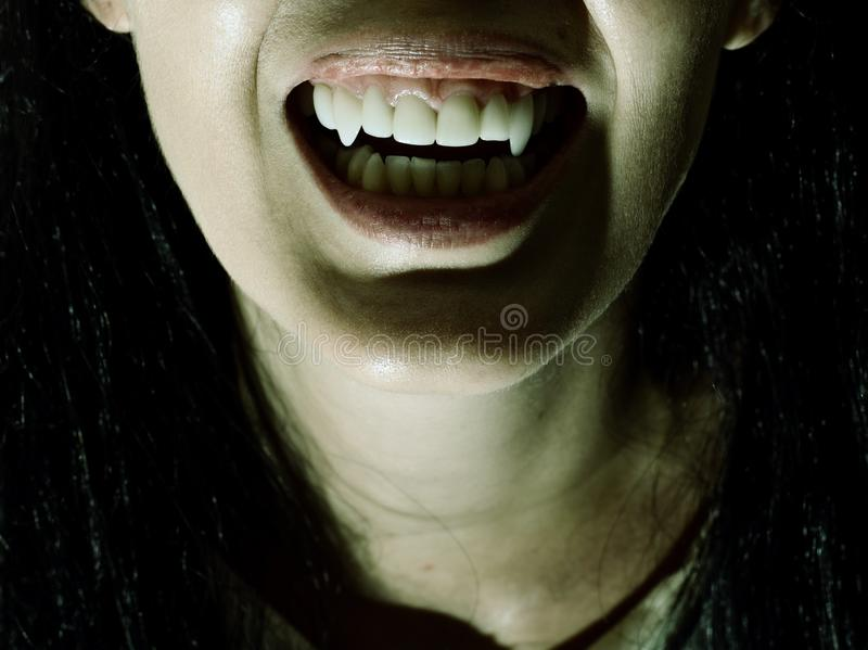 Crazy bloody scary vampire girl with fangs. Halloween horror. Crazy bloody scary vampire girl with fangs screaming on black background stock photography