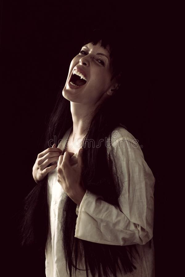 Crazy bloody scary vampire girl with fangs. Halloween horror. Crazy bloody scary vampire girl with fangs screaming on black background royalty free stock photos
