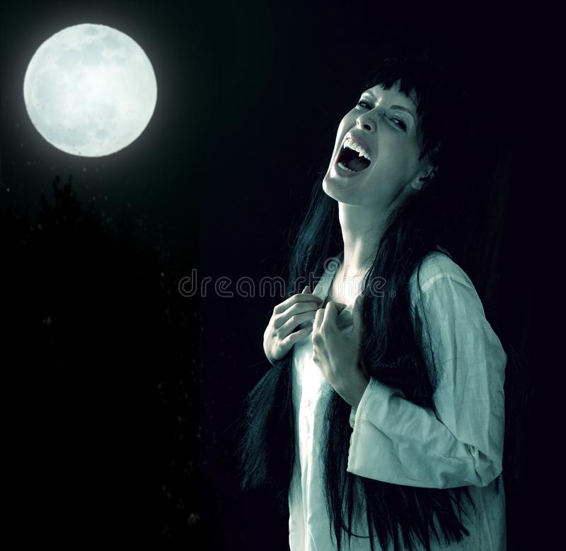 Crazy bloody scary vampire girl with fangs. Halloween horror. Crazy bloody scary vampire girl with fangs screaming on black background stock images