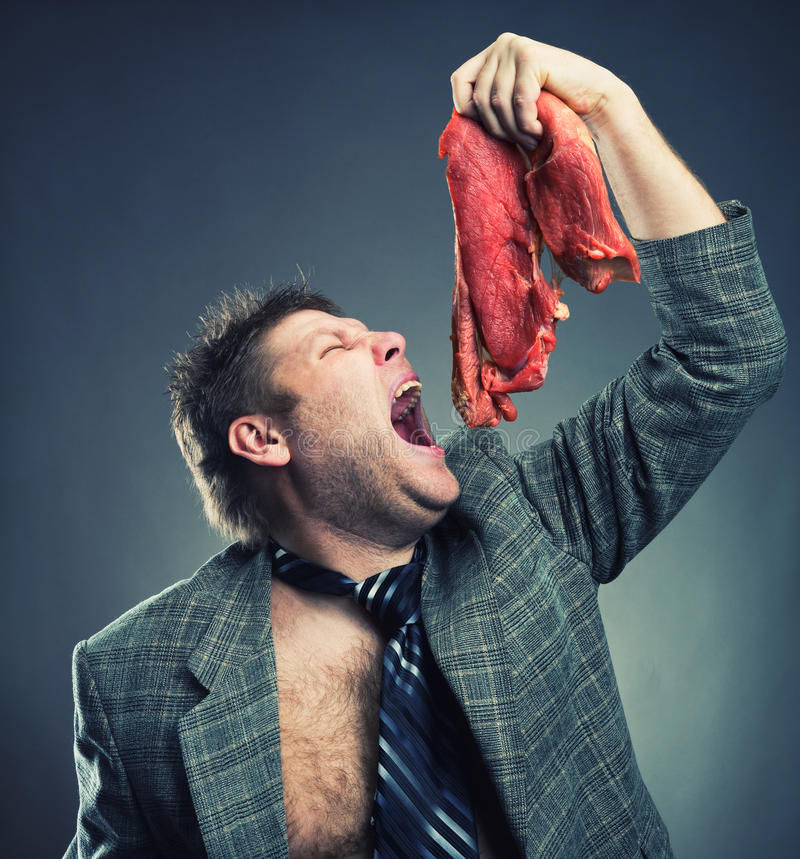 Crazy businessman with meat. Crazy businessman eating raw meat royalty free stock image