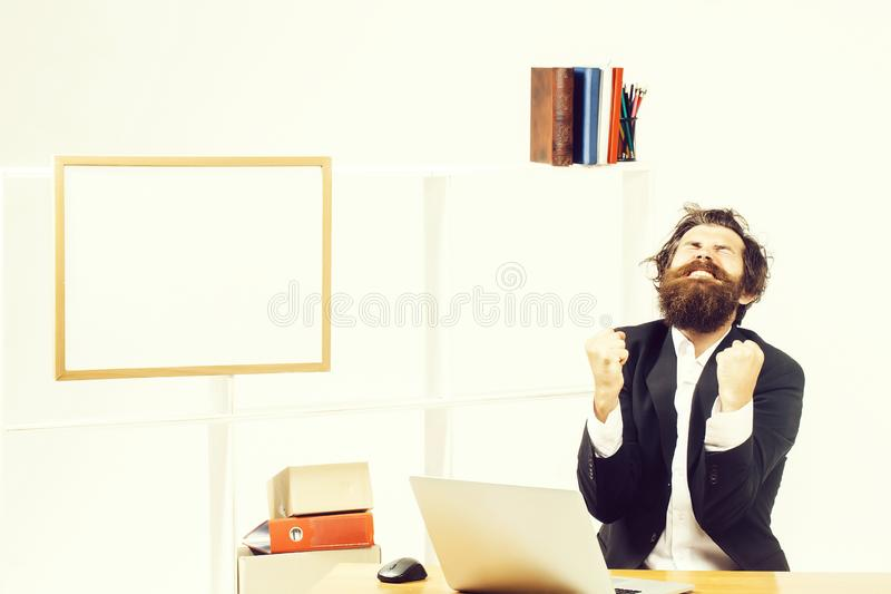 Crazy businessman rejoices in office. Funny crazy bearded young businessman rejoices clenching his fists at desk in office stock photo