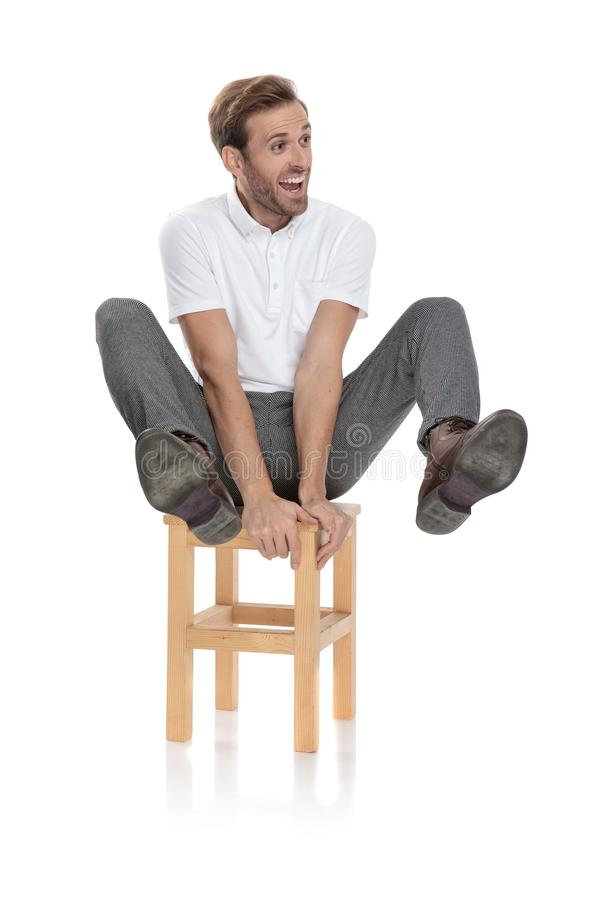 Crazy casual man sitting and holds legs in the air stock photos