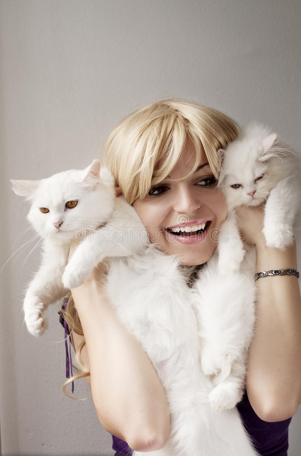 Crazy cat lady. Girl holding two white cats royalty free stock photo