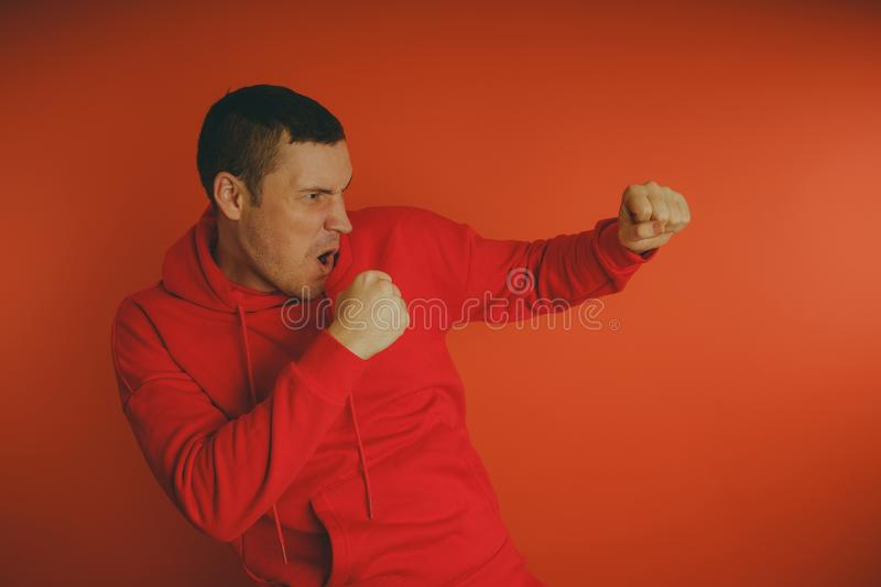 Crazy and charismatic guy posing on an orange background. A man in a red tracksuit. stock images