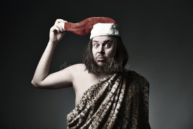 Crazy Christmas. Wild man in leopard skin wear Santa Claus hat royalty free stock photos