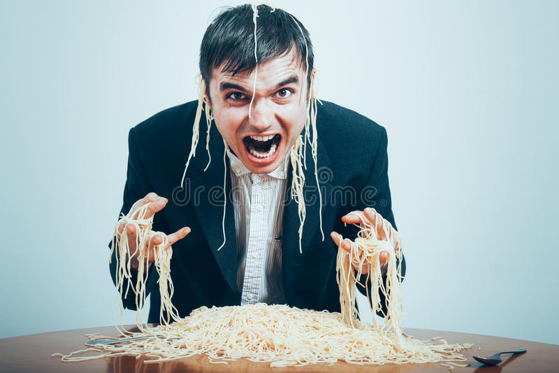 Crazy consumerism. Concept. Mad nasty businessman eating pasta on the table royalty free stock images