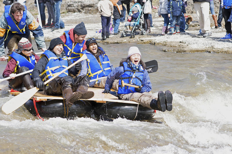 Crazy Craft River Race, Port Hope, March 31/2012. Participants paddle a home made raft through the Ganaraska River rapids on March 31, 2012 in Port Hope, Ontario stock image