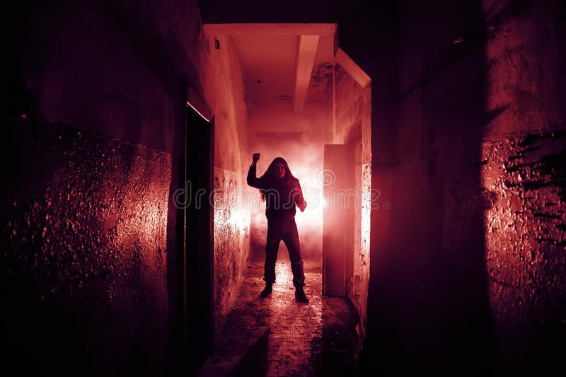 Crazy criminal killer or robber or rapist with knife in hand in dark scary corridor, horror and thriller atmosphere, red toned.  royalty free stock images