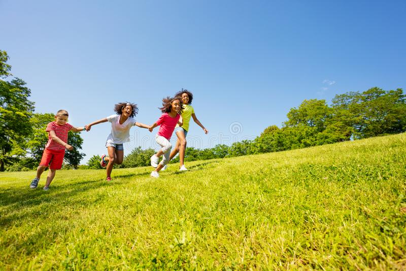 Crazy cute happy kids run in park holding hands stock photos