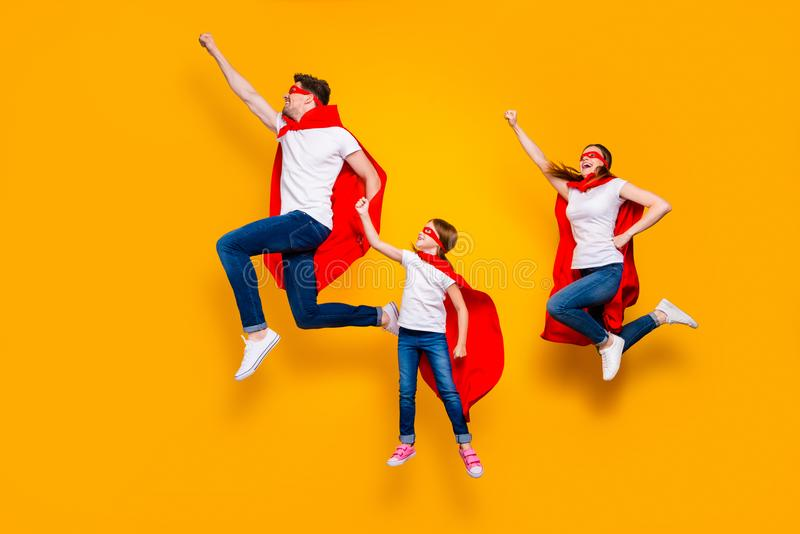 Crazy dad mom and foxy daughter moving up air raise fists wear superhero capes isolated yellow background. Crazy dad mom and foxy, daughter moving up air raise royalty free stock image