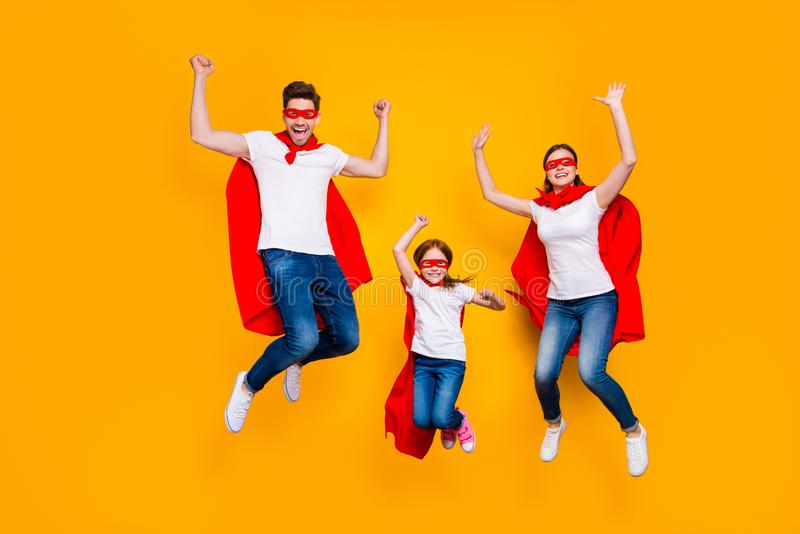 Crazy daddy mommy and foxy daughter jumping high wear cartoon superhero capes isolated yellow background. Crazy daddy mommy and foxy, daughter jumping high wear royalty free stock photos