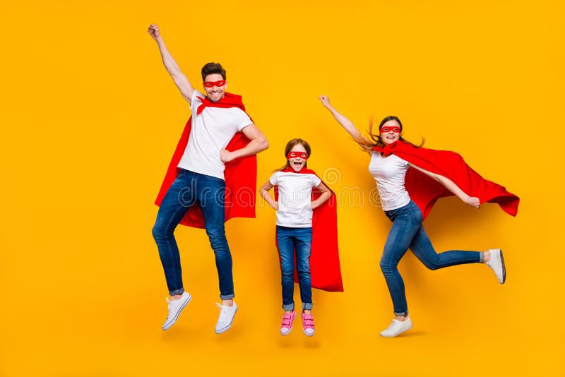 Crazy daddy mommy and foxy daughter moving up air wear cartoon superhero capes isolated yellow background. Crazy daddy mommy and foxy, daughter moving up air stock photography