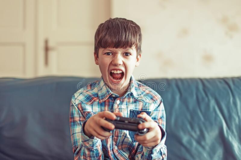 Crazy dependent kid shouting while playing video game royalty free stock photography