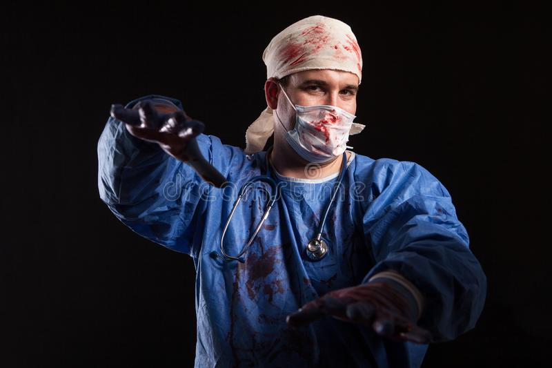 Crazy Doctor with a surgeon mask and scrubs splattered with blood for halloween. Dangerous doctor over black background stock photos