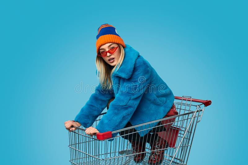 Crazy female in shopping cart. Insane female dapper in bright outfit looking at camera while riding trolley during shopping against blue background royalty free stock images
