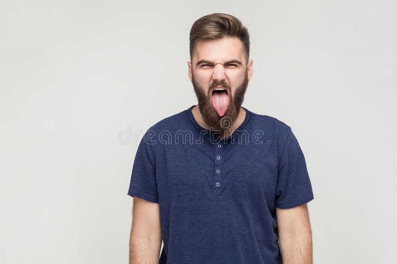 Crazy and fun concept. Bearded young adult man showing tongue. At camera and have a happiness look. Studio shot, isolated on gray background royalty free stock images