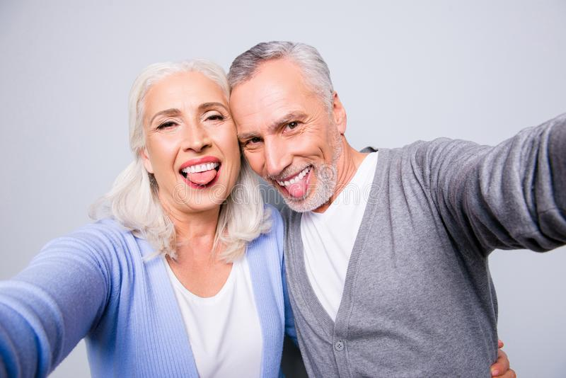 Crazy funky funny elderly couple are taking selfie using smartphone and showing tongues, isolated on grey background royalty free stock photography