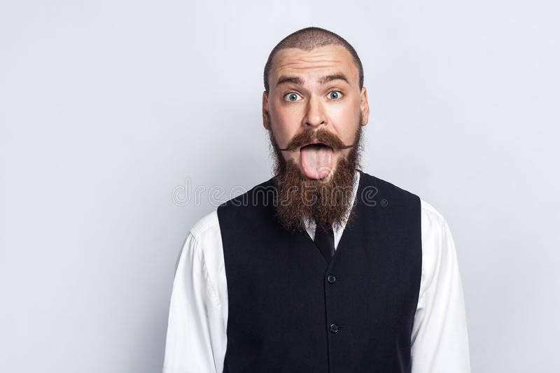 Crazy Funny face. Handsome businessman with beard and handlebar mustache looking at camera with tongue out. Studio shot, on gray background stock photo