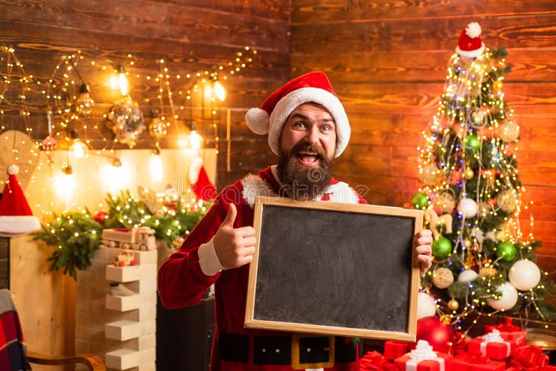Crazy, funny Hipster Santa. New year Christmas concept. . Bearded man in Christmas sweater witd text board. Christmas royalty free stock photo