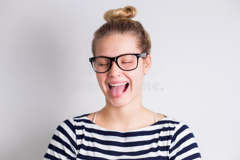 Crazy funny young blond woman in glasses showing tongue and smiling on white background stock photos