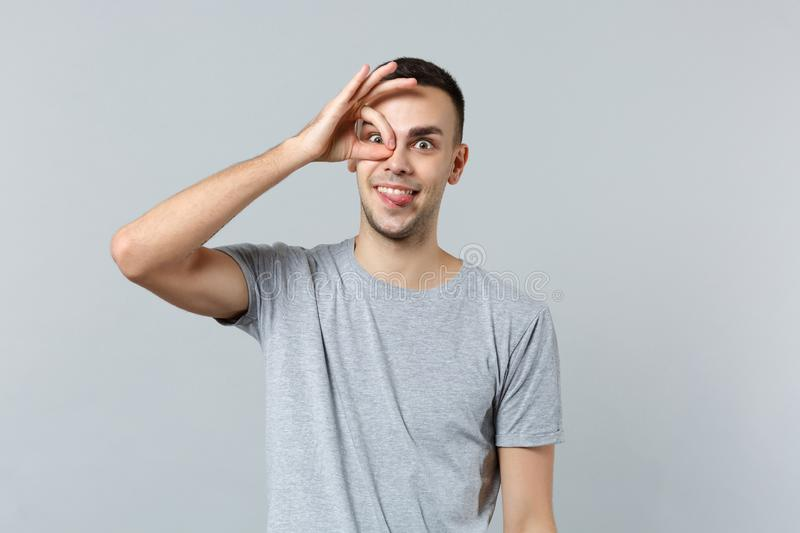 Crazy funny young man in casual clothes showing tongue holding hand near eye imitating glasses or binoculars isolated on. Grey background. People sincere stock photos