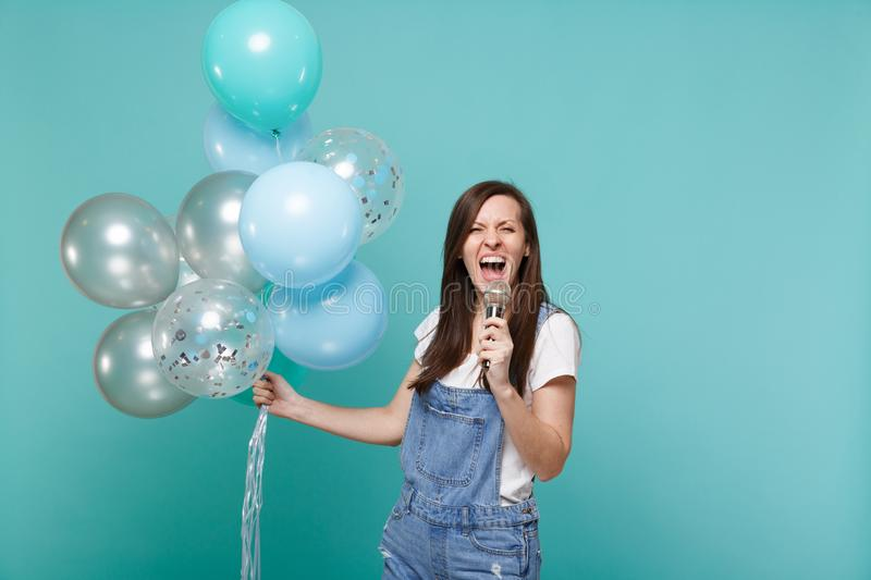 Crazy funny young woman in denim clothes sing song in microphone, celebrating and holding colorful air balloons isolated. On blue turquoise background. Birthday royalty free stock image