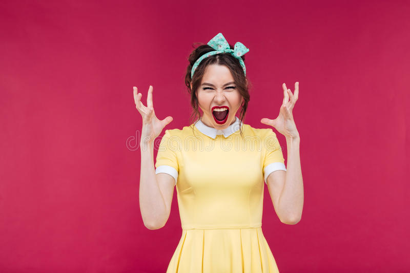 Crazy furious young woman standing and shouting royalty free stock photography
