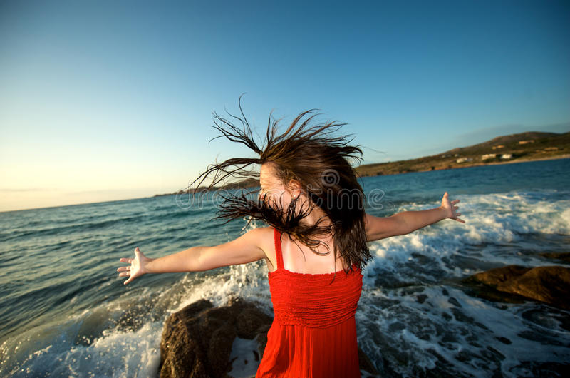 Crazy girl on the beach. Pretty girl moving her hair on the beach at sunset time royalty free stock photo