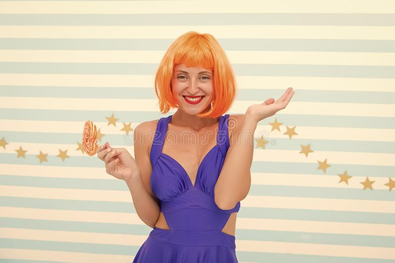 Crazy girl in playful mood. Cool girl with lollipop. Sexy woman. Fashion girl with orange hair having fun. happy pinup. Model with lollipop in hand. Sweet look stock photo