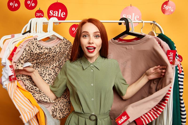Crazy girl standing among clothes on hangers stock images