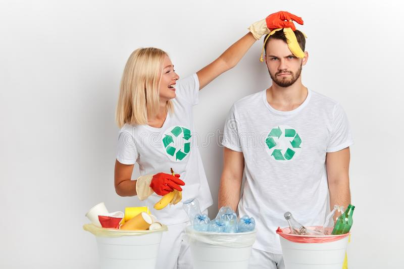 Crazy girl in white T-shirt putting banana peel on her man`s head royalty free stock images